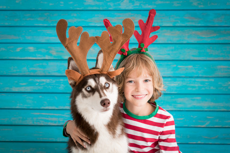 Happy child and dog on Christmas eve. Kid and pet dressed in Santa hat. Stock Photo