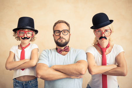 Funny man, woman and kid with fake mustache. Happy family playing in home Stok Fotoğraf - 87847660