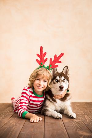 Glückliches Kind und Hund am Weihnachtsabend. Kind und Haustier kleideten in Santa Claus-Hut an. Mädchen, das zu Hause Spaß mit Schlittenhund hat. Chinesisches Kalender-Neujahrs-Konzept Standard-Bild - 87855238
