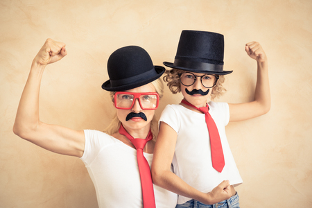 Funny woman and kid with fake mustache. Happy family playing in home