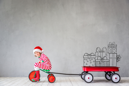 Happy child in Christmas time. Funny kid playing at home. Xmas winter holiday concept Stockfoto