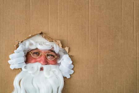 Santa Claus looking through hole on cardboard. Christmas Xmas holiday concept Stock Photo