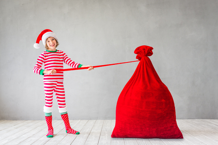 Happy child with Christmas bag Kid having fun at home. Xmas holiday concept