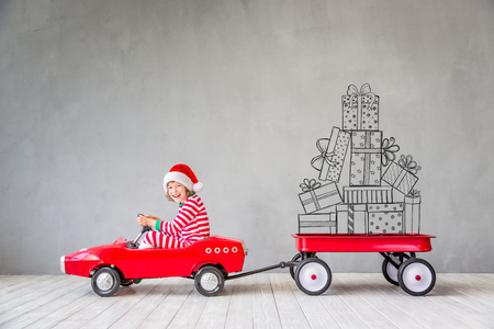 Happy child with Christmas gift. Kid having fun at home. Xmas holiday concept Foto de archivo