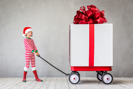 Happy child with Christmas gift. Kid having fun at home. Xmas holiday concept Stock Photo