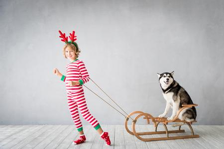 クリスマスイブに幸せな子供と犬。子供とペットはサンタクロースの帽子をかぶっています。自宅でハスキーを楽しんでいる女の子。中国暦の新年