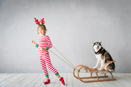 Happy child and dog on Christmas eve. Kid and pet dressed in Santa Claus hat. Girl having fun with husky at home. Chinese calendar new year concept Stok Fotoğraf