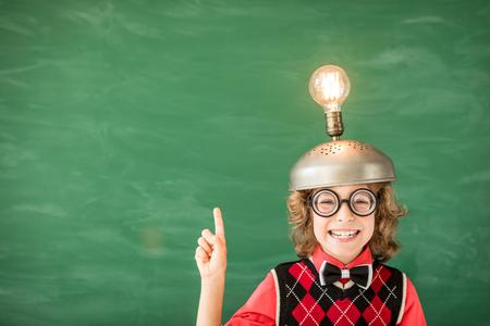 Retrato de criança em sala de aula. Garoto com fone de ouvido de realidade virtual de brinquedo em classe. Conceito de tecnologia de sucesso, ideia e inovação. De volta à escola Foto de archivo