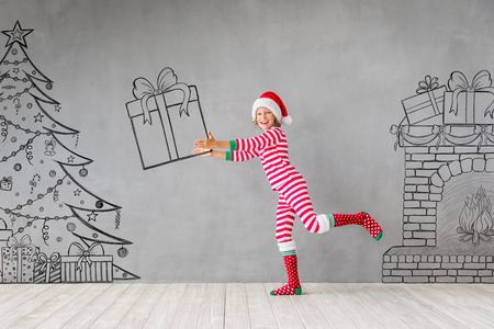 Happy child in Christmas time. Funny kid playing at home. Xmas winter holiday concept Stock Photo