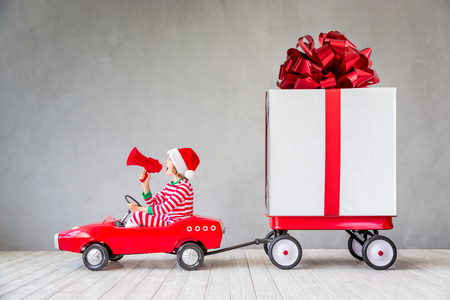 Happy child with Christmas gift. Kid having fun at home. Xmas holiday concept Archivio Fotografico