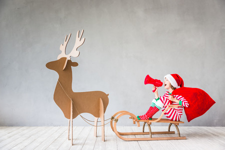 Happy child riding Christmas sleigh. Kid having fun at home. Xmas holiday concept