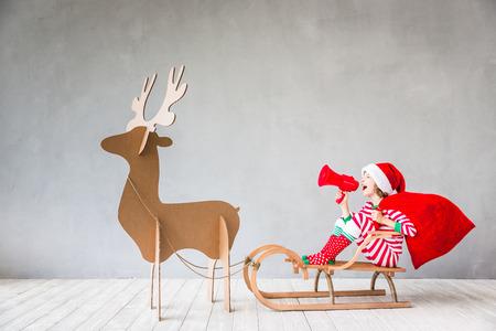 Szczęśliwe dziecko jazdy świąteczne sanie. Dziecko, zabawy w domu. Koncepcja święta Xmas