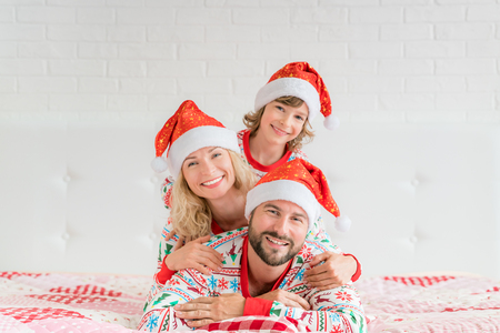 Happy family wearing Santa Claus hats lying on bed. Mother; father and child having fun in Christmas time. Man, woman and kid relaxing at home. Winter holiday Xmas and New Year concept