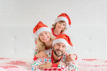 Heureuse famille portant des chapeaux de père Noël se trouvant sur le lit. Mère; père et enfant s'amusant au moment de Noël. Homme, femme et enfant se détendre à la maison. Concept de vacances de Noël et nouvel an