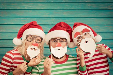 Héhé, jouant à la maison. Père drôle; mère et enfant le soir de Noël. Concept de vacances d'hiver de Noël