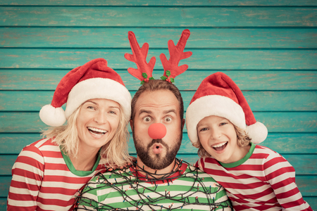 Happy family playing at home. Funny father; mother and child on Christmas eve. Xmas winter holiday concept Standard-Bild