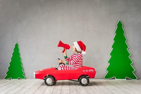 Glückliches Kind, das zu Hause spielt. Lustiges Kind am Weihnachtsabend. Weihnachtswinter-Feiertagskonzept Standard-Bild - 89182916