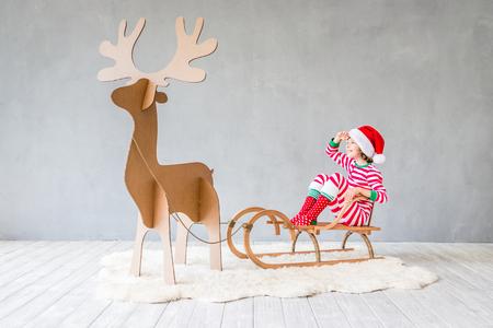 De gelukkige slee van kind berijdende Kerstmis. Kind plezier thuis. Xmas vakantie concept
