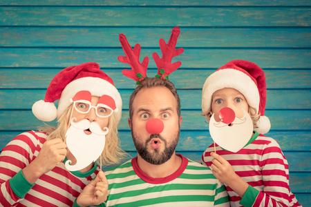 Glückliche Familie, die zu Hause spielt. Lustiger Vater; Mutter und Kind am Heiligabend. Weihnachtswinter-Feiertagskonzept