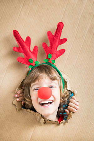 Funny kid looking through hole on cardboard. Child playing at home. Christmas holiday concept. Copy space.