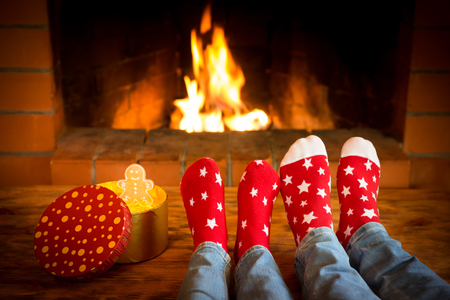 Mother and child near fireplace. People relaxing at home. Winter holiday Christmas and New Year concept