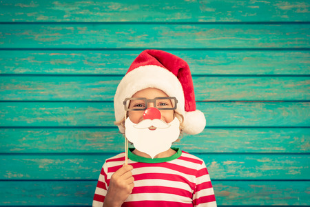 Happy child playing at home. Funny kid on Christmas eve. Xmas winter holiday concept