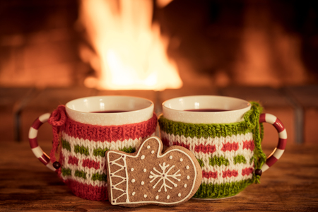 Two Christmas cups of mulled wine near fireplace. Winter holiday Xmas and New Year concept Stock Photo