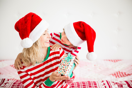 Happy family wearing Santa Claus hats sitting on bed. Mother and child having fun in Christmas time. Woman and kid relaxing at home. Winter holiday Xmas and New Year concept