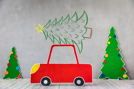 Cardboard car and Christmas tree. Xmas holiday concept Stock Photo