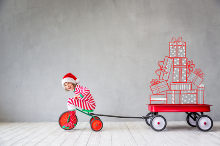 Happy child in Christmas time. Funny kid playing at home. Xmas winter holiday concept Archivio Fotografico