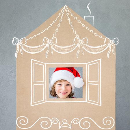 Happy child in Christmas time. Funny kid playing at home. Xmas winter holiday concept Reklamní fotografie