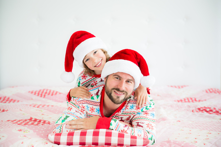 Happy family wearing Santa Claus hats lying on bed. Father and child having fun in Christmas time. Man and kid relaxing at home. Winter holiday Xmas and New Year concept Stock Photo