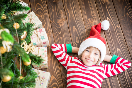Happy child lying on wooden floor. Funny kid on Christmas eve. Xmas holiday concept Stock Photo