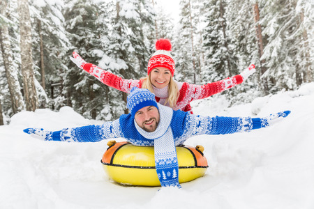 Happy couple having fun outdoor. Man and woman playing in winter time. Active healthy lifestyle concept