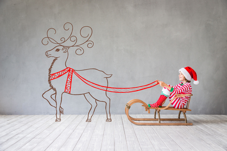 Happy child in Christmas time. Funny kid playing at home. Xmas winter holiday concept Banco de Imagens