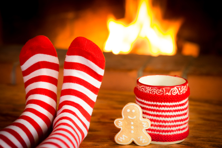 Child in Christmas socks near fireplace. Kid relaxing at home. Winter holiday Xmas and New Year concept