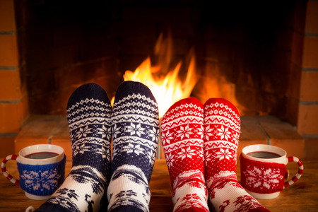 Couple in Christmas socks near fireplace. Friends having fun together. People relaxing at home. Winter holiday Xmas and New Year concept Фото со стока