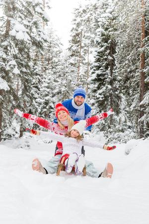 アウトドアを楽しんで幸せな家族。冬の間に遊んでいる子供、母、父。アクティブ健康的なライフスタイルコンセプト