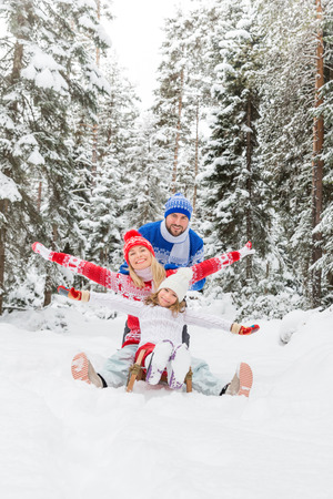 Happy family having fun outdoor. Child, mother and father playing in winter time. Active healthy lifestyle concept