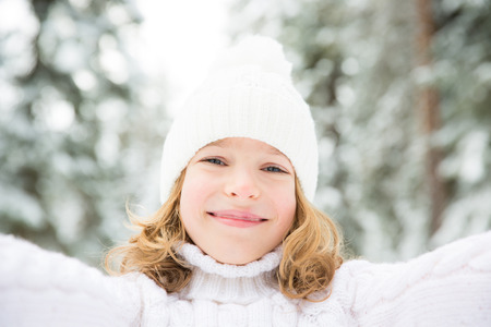 Happy child playing outdoor. Kid having fun in winter park. Healthy active lifestyle concept