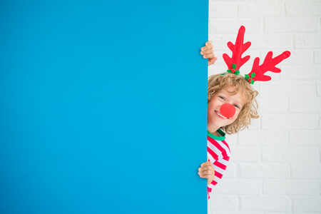 Funny kid holding cardboard banner blank. Child playing at home. Christmas holiday concept. Copy space. Stock Photo