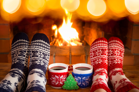Couple in Christmas socks near fireplace. Friends having fun together. People relaxing at home. Winter holiday Xmas and New Year concept 스톡 콘텐츠