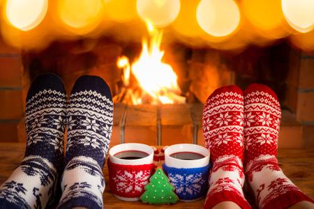 Paare in den Weihnachtssocken nähern sich Kamin. Freunde, die zusammen Spaß haben. Leute, die sich zu Hause entspannen. Winterurlaub Weihnachten und Neujahr Konzept