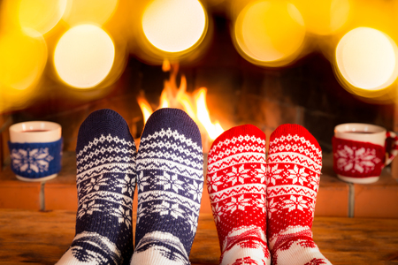 Couple in Christmas socks near fireplace.