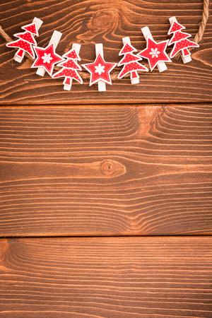 木製の背景にクリスマスの装飾品。ロープに掛かるクリスマスツリーの装飾 写真素材