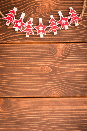 Christmas ornament on wooden background. Christmas-tree decoration hanging on rope