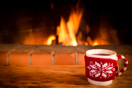 Christmas cup of mulled wine near fireplace. Winter holiday Xmas and New Year concept