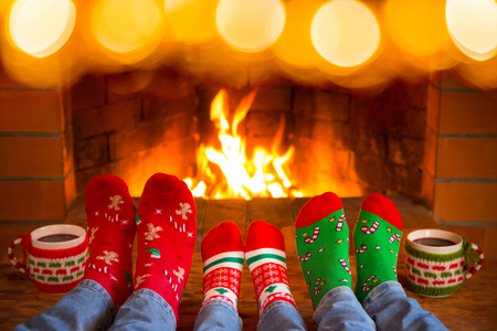 Family in Christmas socks near fireplace. Mother; father and child having fun together. People relaxing at home. Winter holiday Xmas and New Year concept