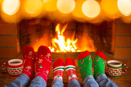 Familie in den Weihnachtssocken nahe Kamin. Mutter; Vater und Kind haben Spaß zusammen. Leute, die sich zu Hause entspannen. Winterurlaub Weihnachten und Neujahr Konzept Standard-Bild