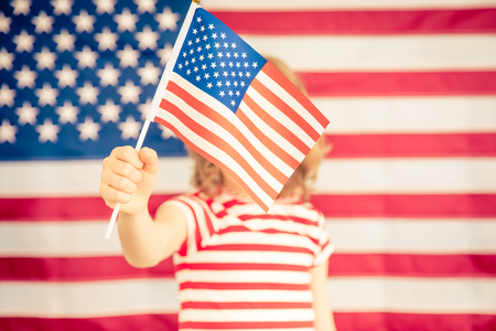 Child holding American flag. 4th of July, Independence day holiday. Patriotism and democracy concept